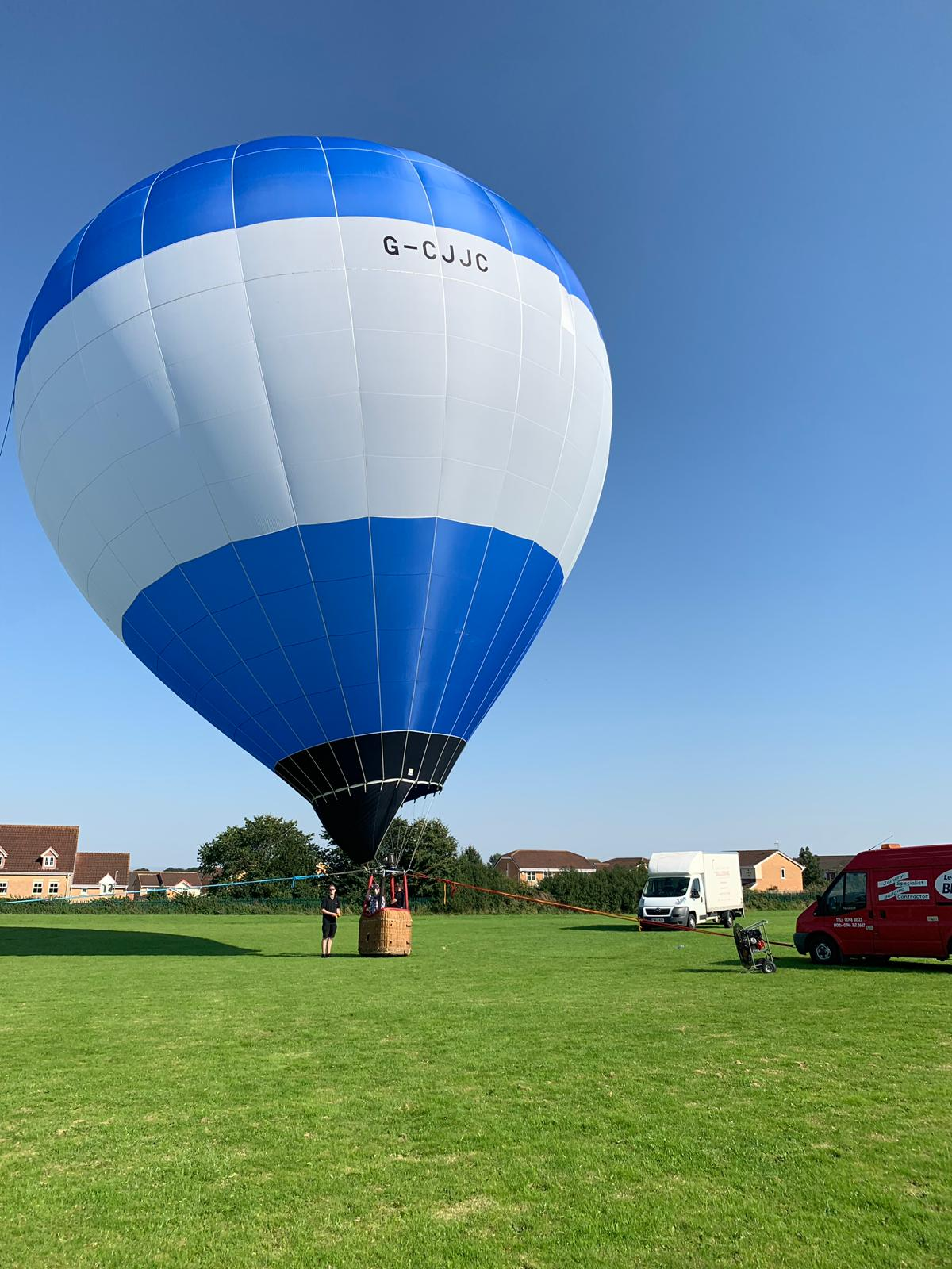 A blue and white balloon in a large field, representing unbranded tethering for events.